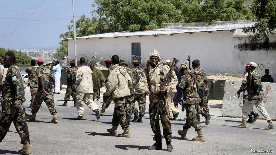 Somali soldiers patrol at the front gate of the presidential palace following a suicide bomb attack in Mogadishu, Somalia, January 29, 2013.