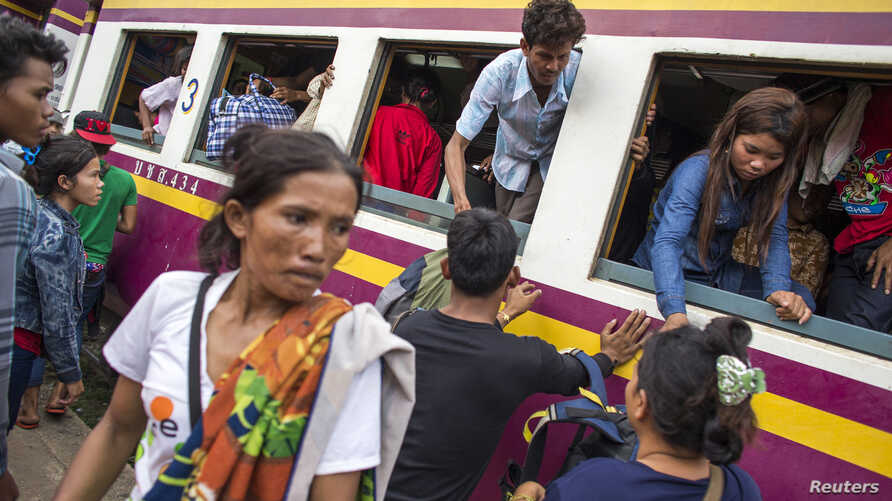 Cambodian workers get off a train as they prepare to migrate back to Cambodia at Aranyaprathet train station in Sa Kaew, June 15, 2014.