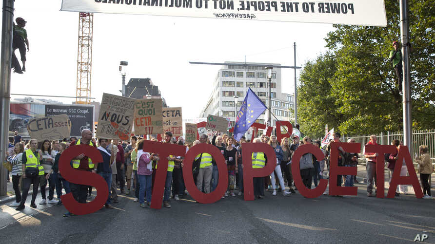 FILE - Protestors hold an anti-CETA banner during a demonstration against international trade agreements, in Brussels.