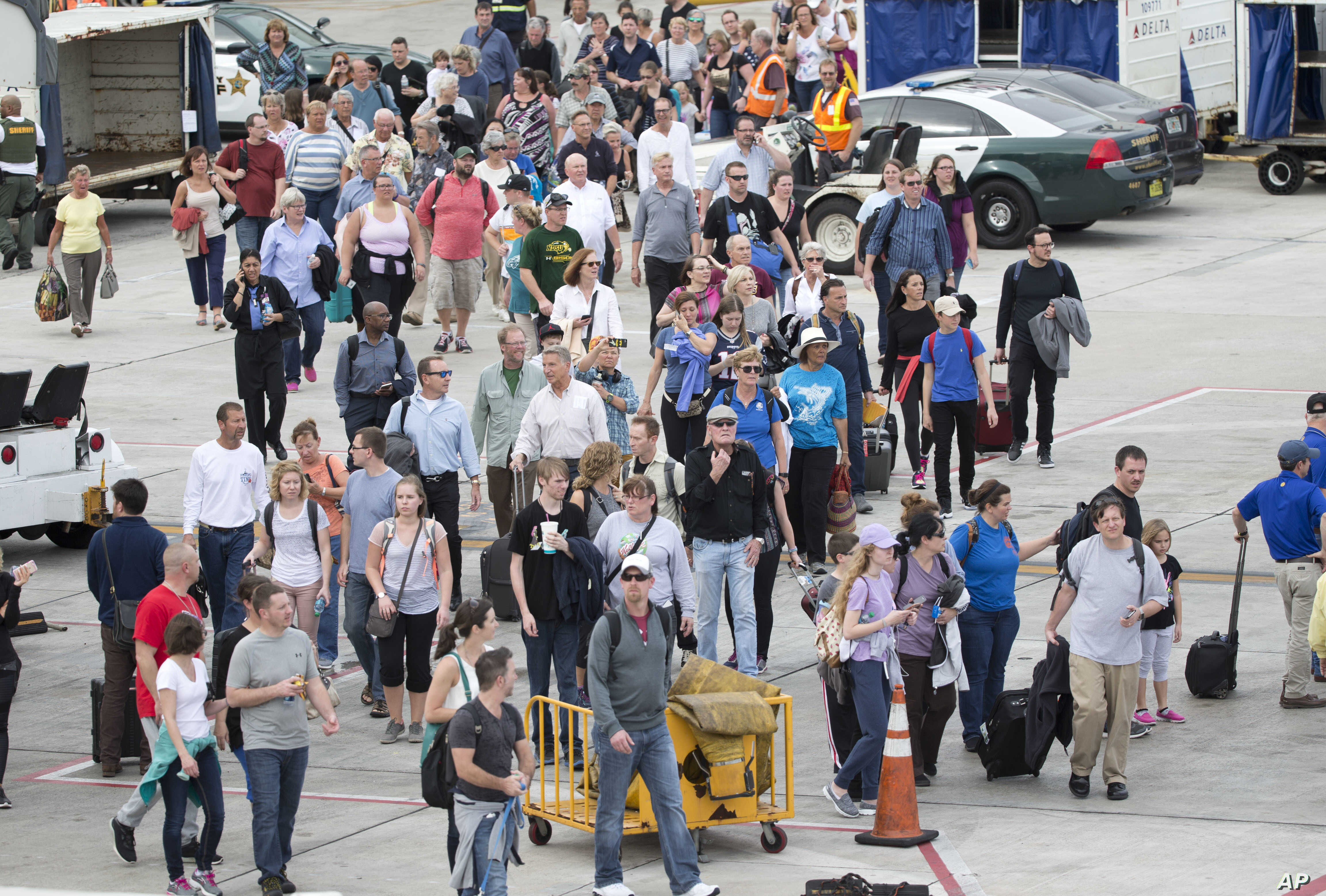 Passengers are shown on the tarmac outside Fort Lauderdale–Hollywood International Airport, Friday, Jan. 6, 2017, in Fort Lauderdale, Florida, after a shooter opened fire inside a terminal of the airport, killing several people and wounding others be