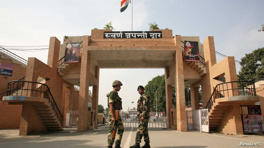 India's Border Security Force (BSF) soldiers patrol in front of the golden jubilee gate at the Wagah border, on the outskirts of the northern Indian city of Amritsar, Nov. 3, 2014.