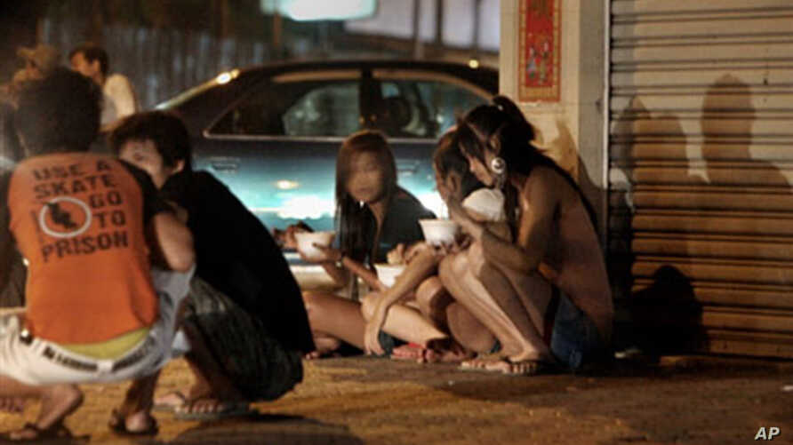 Cambodian sex workers sit on a sidewalk in a street of Phnom Penh (2008 file photo)