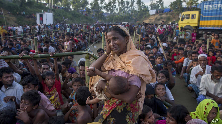 A Rohingya Muslim woman, who crossed over from Myanmar into Bangladesh, wipes her sweat as she waits to receive aid during its distribution near Balukhali refugee camp, Bangladesh, Sept. 25, 2017.