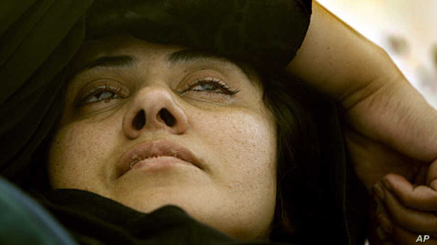 Visibly exhausted, Afghan lawmaker Semin Barakzai lays in her tent as she continues her hunger strike for an eighth consecutive day in Kabul, Afghanistan, Sunday October 9, 2011.