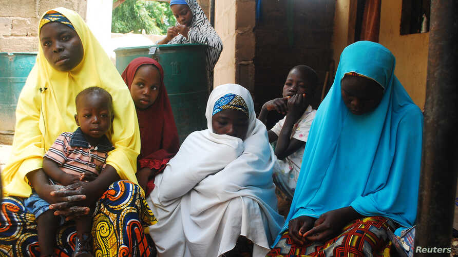 FILE - Women and children, who escaped attacks by Boko Haram militants, sit together at an internally displaced persons camp at Wurojuli, Gombe State, Sept. 2, 2014.