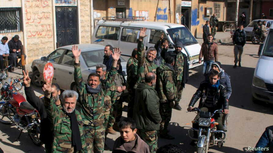 Fighters loyal to Syria's President Bashar al-Assad celebrate with residents of Nubul and al-Zahraa after breaking the siege of their towns in the northern Aleppo countryside, Syria, in this handout picture provided by SANA, Feb. 4, 2016.