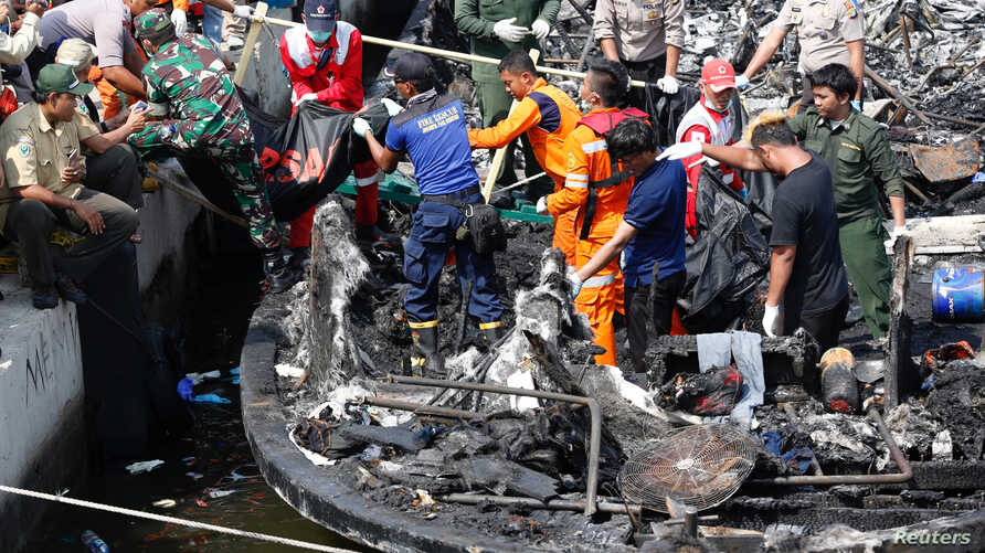 Police, Red Cross and rescue workers remove the remains of victims after a fire ripped through a boat carrying tourists to islands north of the capital, at Muara Angke port  in Jakarta, Indonesia Jan. 1, 2017.