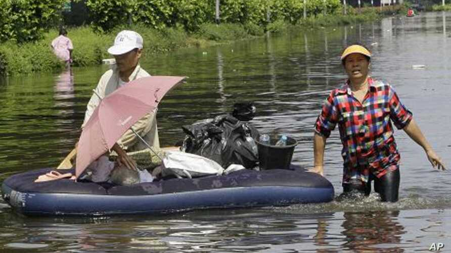 Thai people wade through a flooded area at Don Muang district in Bangkok, Thailand, October 23, 2011.