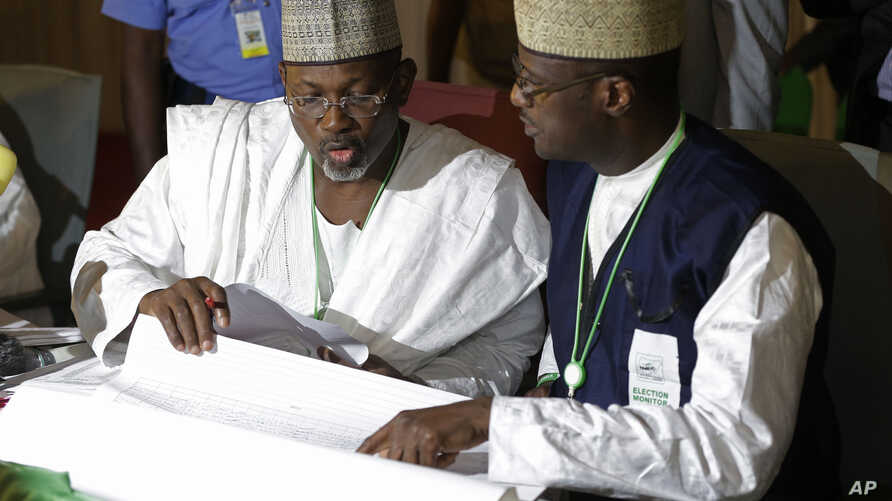 Independent National Electoral Commission chairman, Attahiru Jega, left, views election results at the coalition center in Abuja, Nigeria, Monday, March 30, 2015.