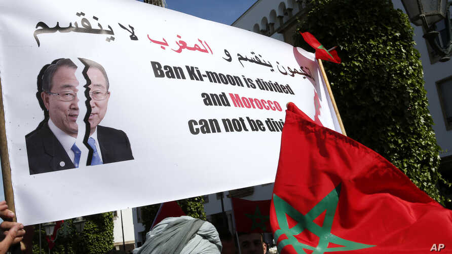 """FILE - Protesters hold a banner and the Moroccan flag at a rally in Rabat, Morocco, as they accuse U.N. Secretary-General Ban Ki-moon of """"abandoning neutrality, objectivity and impartiality"""" during a recent visit to Western Saharan refugee camps in s"""