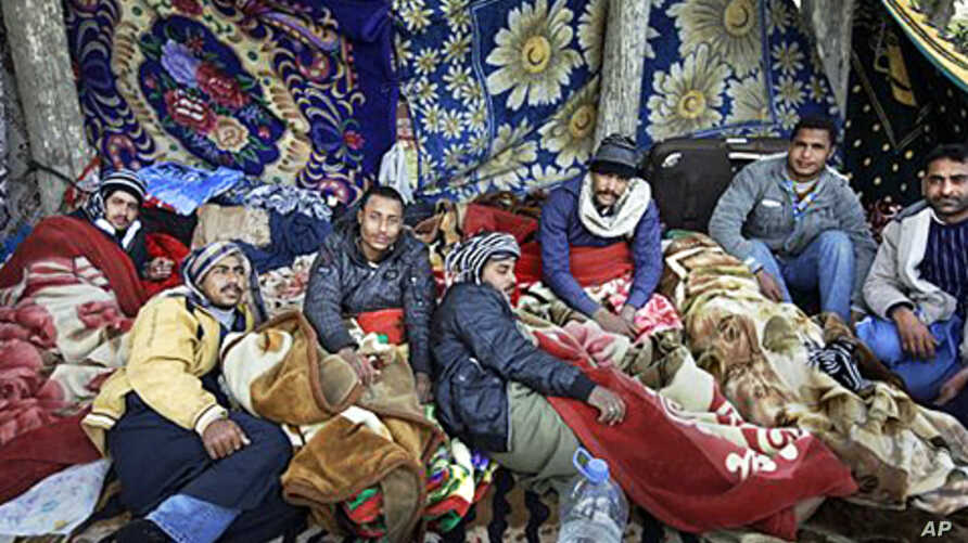 Egyptian migrant workers lie under blankets in a makeshift open-air camp at Tripoli International Airport in Libya, March 1, 2011