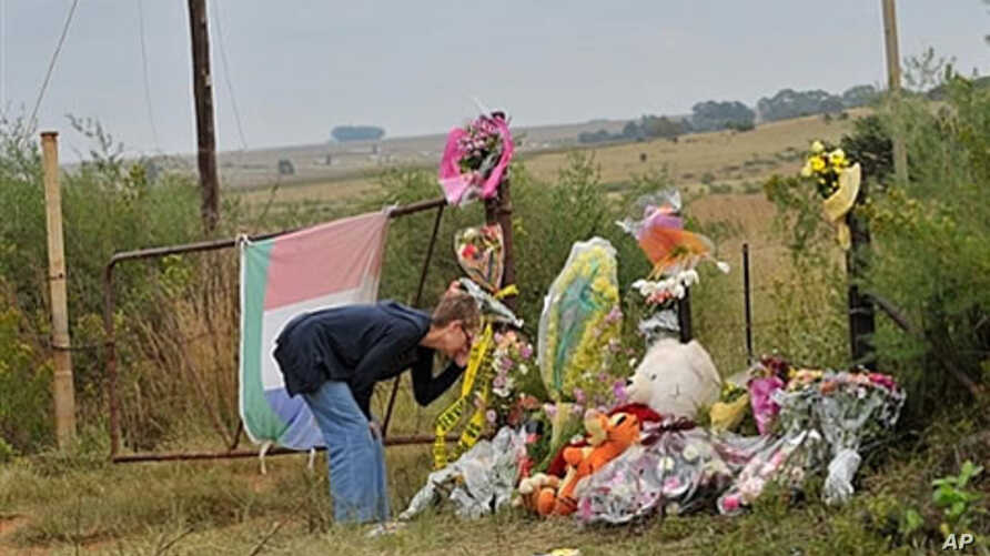 A supporter of African far-right leader Euguene Terre'Blanche looks at flowers and pays tribute in front of the entrance of the farm in Ventersdorp, 05 Apr 2010