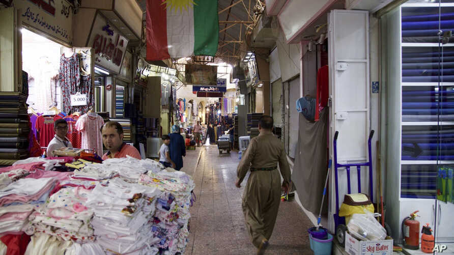 A Kurdish man wearing traditional clothes passes under a Kurdish flag in Irbil's old bazaar, IraqThursday, Aug. 24, 2017. Despite calls from Baghdad and the United States to postpone the vote, Iraq's semi-autonomous Kurdish region is pressing ahead w