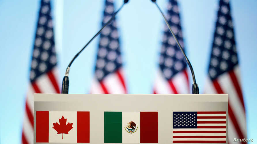 FILE - The flags of Canada, Mexico and the U.S. are seen on a lectern before a joint news conference on the closing of the seventh round of NAFTA talks in Mexico City, Mexico, March 5, 2018.