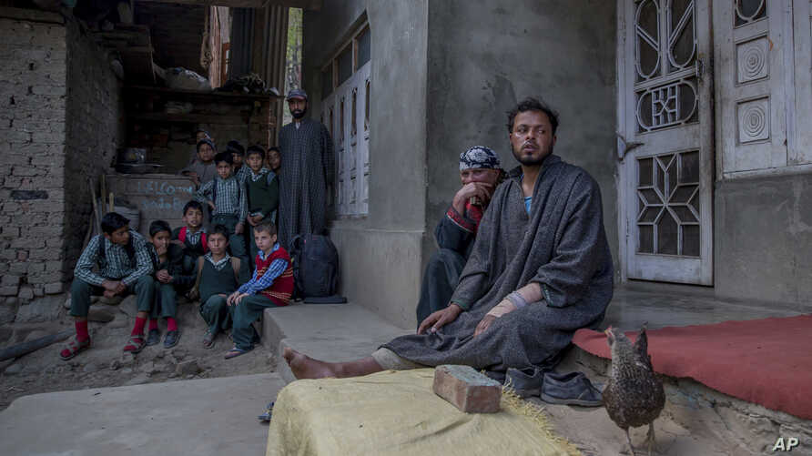 In this April 18, 2017 photo, Kashmiri man Farooq Ahmed Dar, right, sits along with her mother as school children watch from distance at his residence in Chill village, about 60 Kilometers (38 miles) southwest of Srinagar, Indian controlled Kashmir.