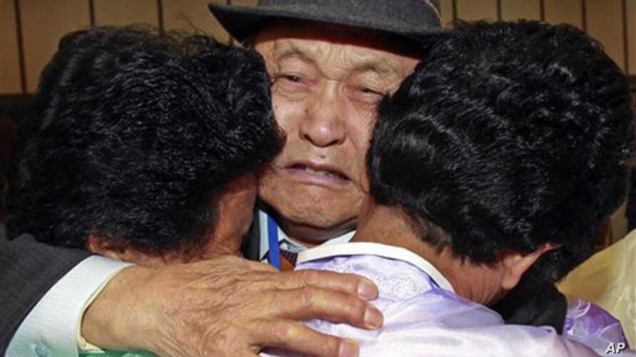 South Korea Lee Pung-no, center, weeps as he hugs with his North Korean daughters during the Separated Family Reunion Meeting at Diamond Mountain in North Korea, 03 Nov 2010