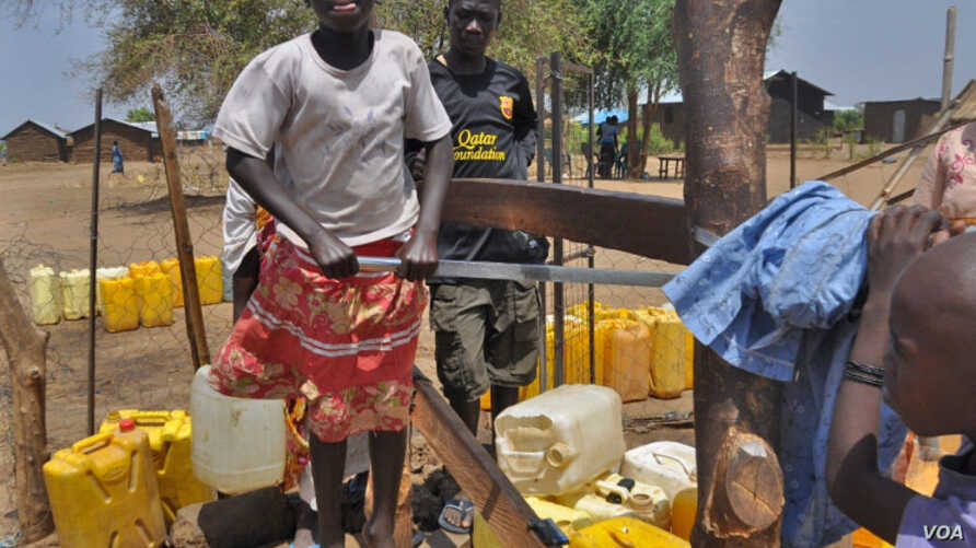 A South Sudanese girl is lifted off the ground as she pumps water at a borehole in Gudere, near Juba. The international community is pumping funds into South Sudan to try to develop its water infrastructure. (VOA/Mugume Davis Rwakaringi)