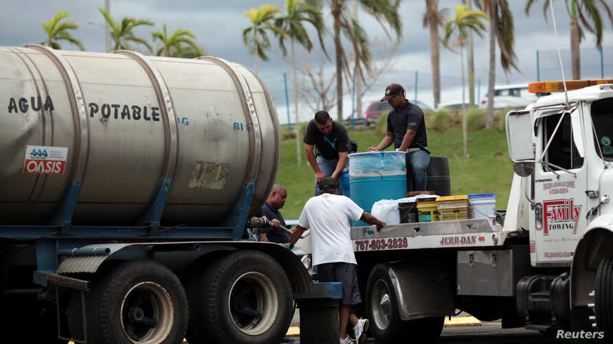 Local residents fill up cans with water in Bayamon following damages caused by Hurricane Maria in Carolina, Puerto Rico, Sept. 30, 2017.