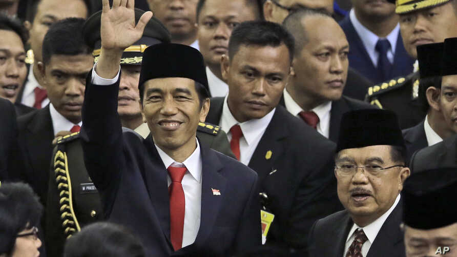 Indonesian President Joko Widodo, center, waves as he walks with his deputy Jusuf Kalla, bottom right with glasses, after their inauguration ceremony at the Parliament building in Jakarta, Indonesia, Monday, Oct. 20, 2014.