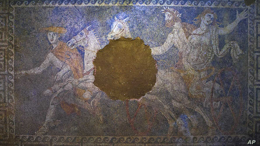 FILE - A damaged mosaic floor showing the Greek god of the underworld, Pluto, abducting the goddess Persephone as the god Hermes looks on, found in a large 4th-century B.C. tomb at Amphipolis, in northern Greece.
