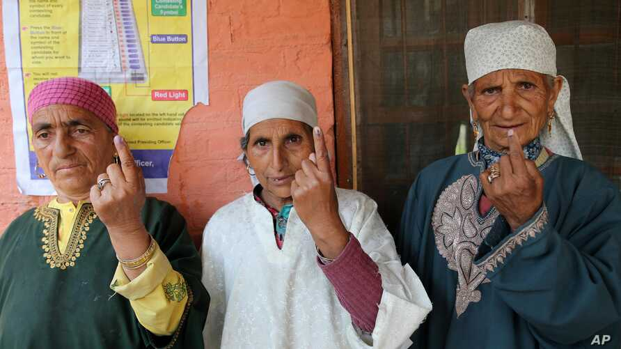 Kashmiri women display the indelible ink mark on their fingers after casting their votes, outside a polling station in Sheeri, about 60 kilometers (37 miles) north of Srinagar, India, May 7, 2014.