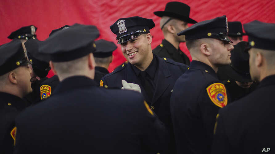Matias Ferreira (center) celebrates with his colleagues during their graduation from the Suffolk County Police Department Academy in Suffolk, N.Y., March 24, 2017. Ferreira, a former U.S. Marine Corps lance corporal who lost his legs below the knee
