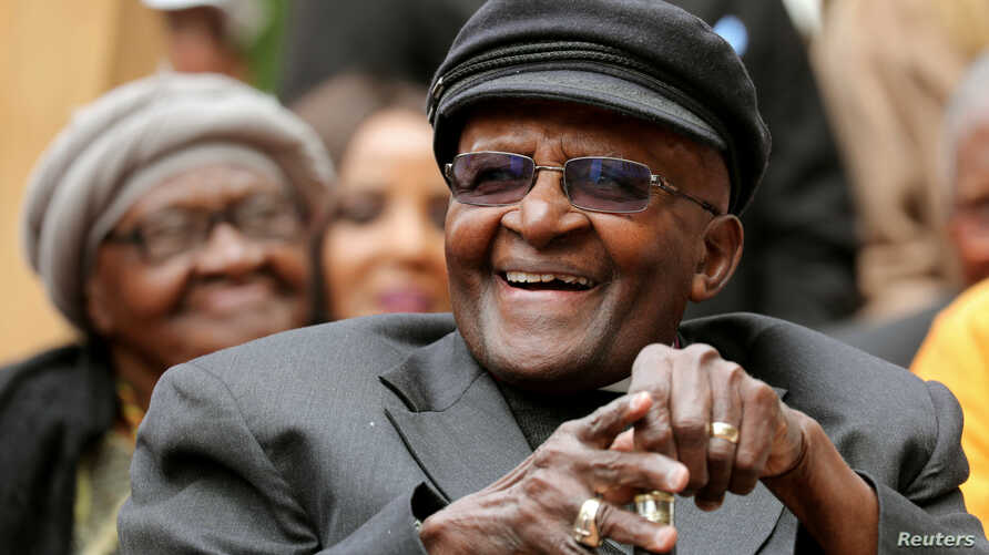 FILE - Archbishop Desmond Tutu laughs as crowds gather to celebrate his birthday by unveiling an arch in his honor outside St. George's Cathedral in Cape Town, South Africa, Oct. 7, 2017.