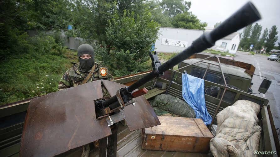 An armed pro-Russian separatist from the so-called Vostok (East) Battalion stands guard at a checkpoint in the eastern Ukrainian city of Donetsk July 8, 2014.
