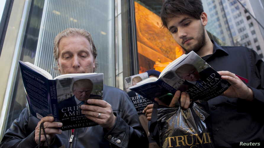 """People read as they wait in line for Republican presidential candidate Donald Trump to sign copies of his new book """"Crippled America"""" in the Manhattan borough of New York, Nov. 3, 2015."""