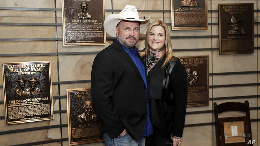 FILE - Country music stars Garth Brooks and Trisha Yearwood pose in the Country Music Hall of Fame, March 27, 2018, in Nashville, Tenn. The couple have been married since 2005.