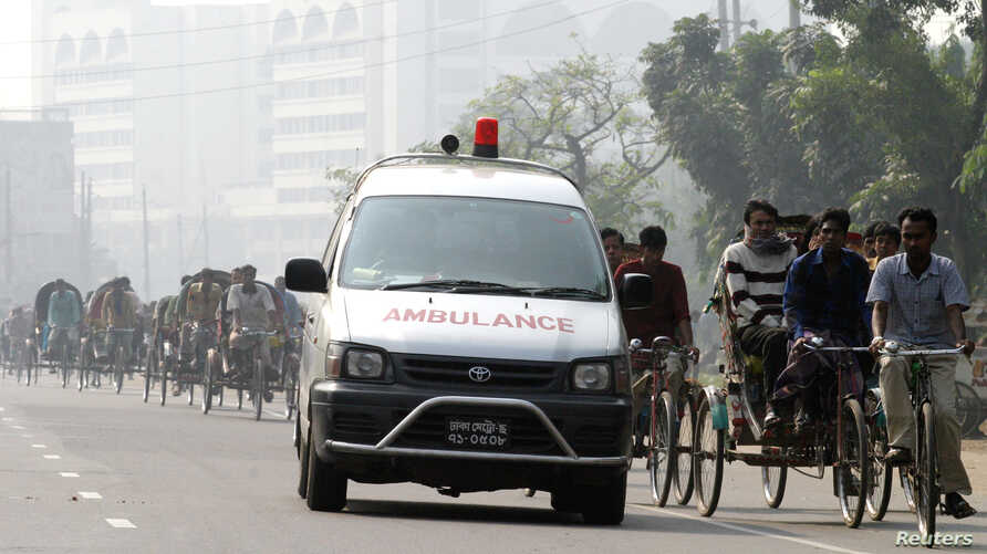 FILE – A traditional ambulance rushes past trishaws on a h
