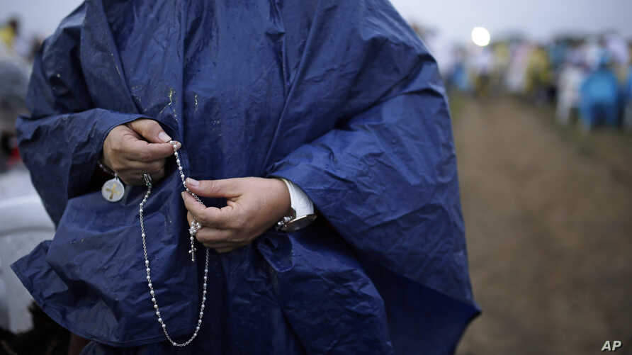 A woman holds a rosary as she waits for the start of a Mass to be celebrated by Pope Francis, in Villavicencio, Colombia, Sept. 8, 2017.