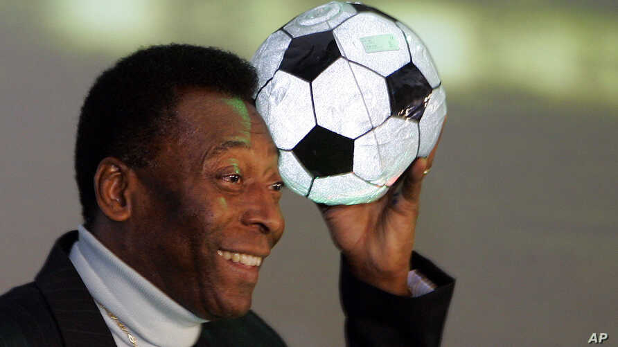 FILE - Brazilian soccer legend Pele poses for photographers with an inflatable soccer ball after a press conference in Berlin, June 7, 2006.