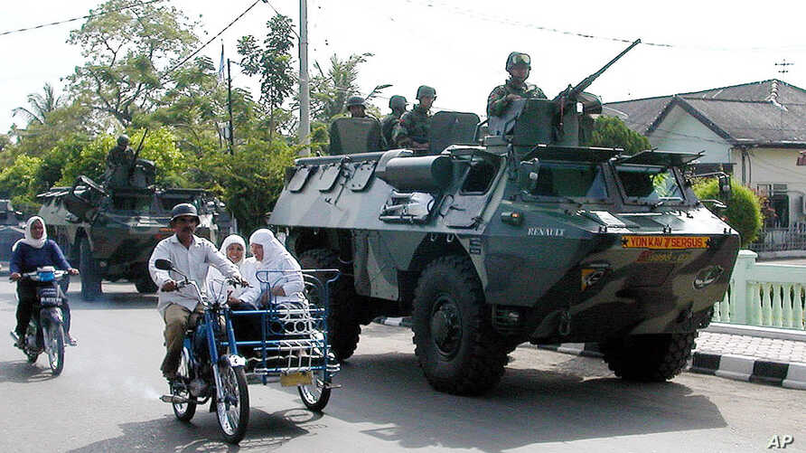 Indonesian soldiers patrol the streets of Lhokseumawe, June 24, 2003, in the restive province of Aceh, Indonesia.