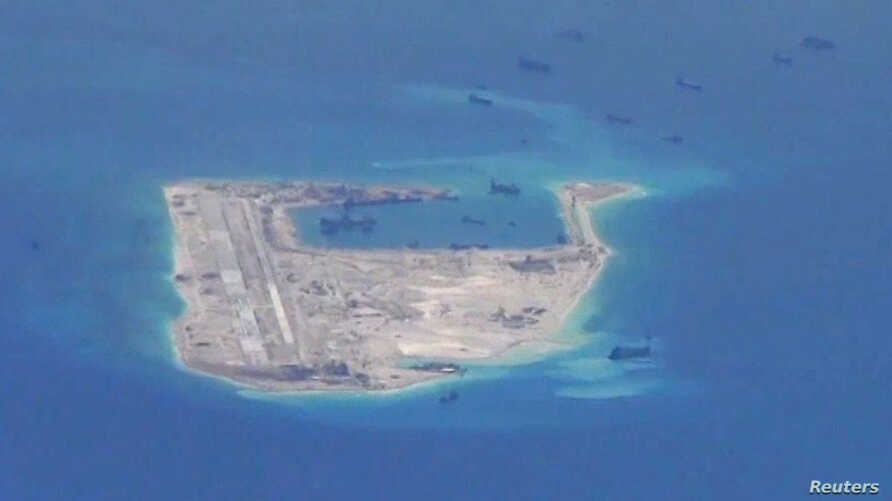 Chinese dredging vessels are purportedly seen in the waters around Fiery Cross Reef in the disputed Spratly Islands in the South China Sea in this still image from video taken by a P-8A Poseidon surveillance aircraft provided by the United States Nav...