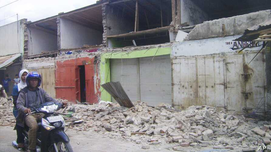 Residents on a motorcycle pass a damaged building after a 6.7 magnitude in the town of Bima, on Indonesia's Sumbawa island,  Nov. 9, 2009. The island was struck by two earthquakes, Jan. 22, 2019, of magnitude 6 and 6.6.
