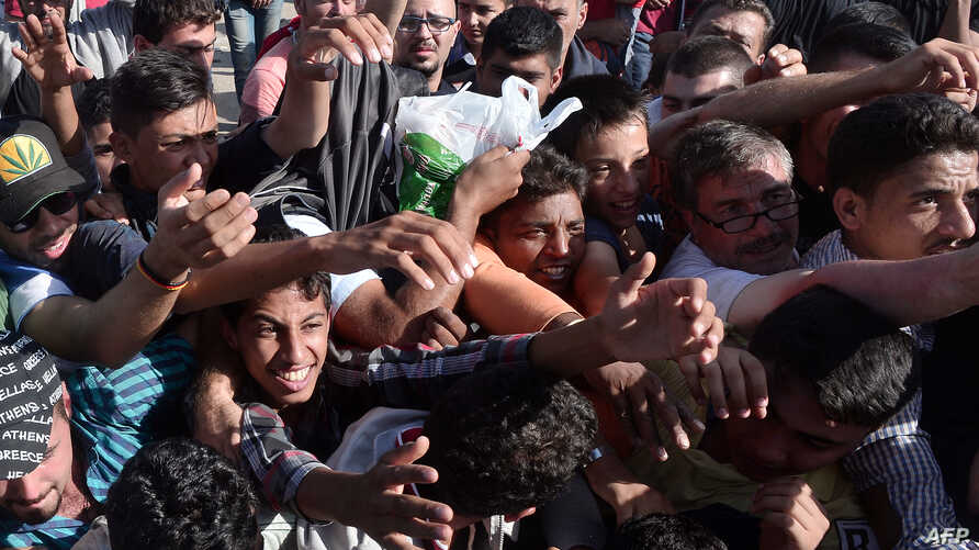 Migrants raise their hands to get some food and water distributed by Caritas on the Greek-FYR Macedonia border near the vilage of Idomeni, Sept. 5, 2015.