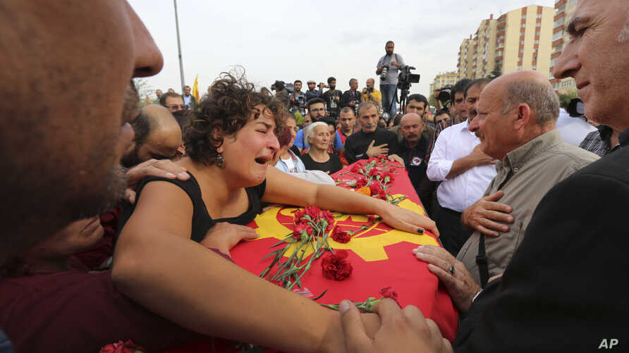A relative cries over the coffin of Korkmaz Tedik, 25, killed in Saturday's bombing attacks, during his funeral, at the Pir Sultan Abdal Cemevi, a place of worship for Turkey's Alevi community in the outskirts of Ankara, Turkey, Sunday, Oct. 11, 2015