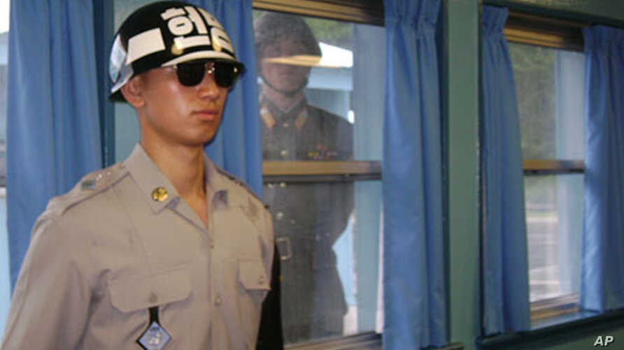 A North Korean soldier looks through a window as a South Korean stands guard during the visit of U.S. Secretary of State Hillary Clinton at the U.N. truce village building that sits on the border of the Demilitarized Zone (DMZ), in Panmunjon, South K