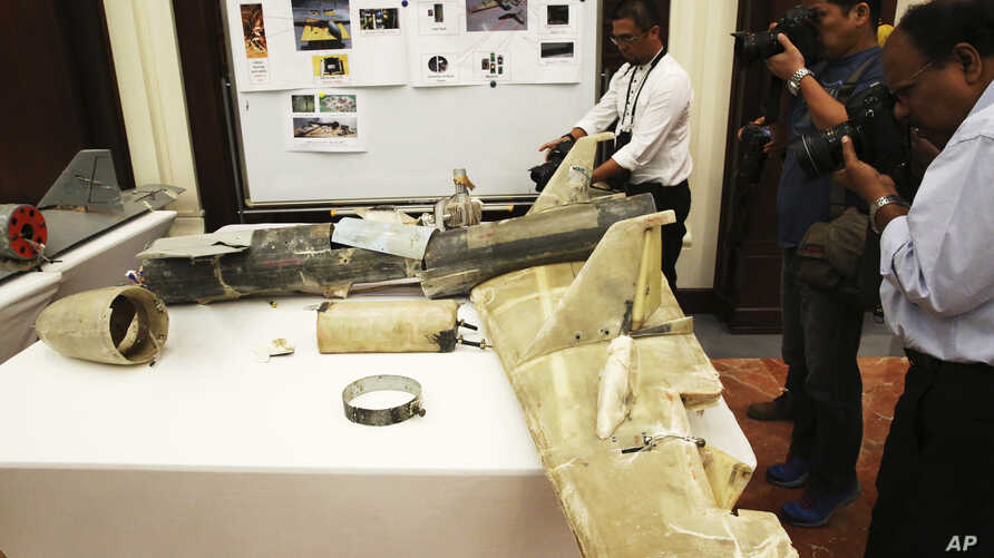 FILE - Photographers take pictures of what officials described as an Iranian Qasef drone captured on the battlefield in Yemen during a news conference in Abu Dhabi, United Arab Emirates, June 19, 2018.