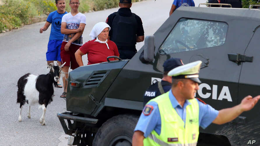 FILE - Albanian police forces, who are offering a $33,000 reward for information leading to an arrest in the shooting deaths of two Czech tourists, seen securing unrelated crime scene about 200 kilometers (125 miles) south of Tirana, June 24, 2015.