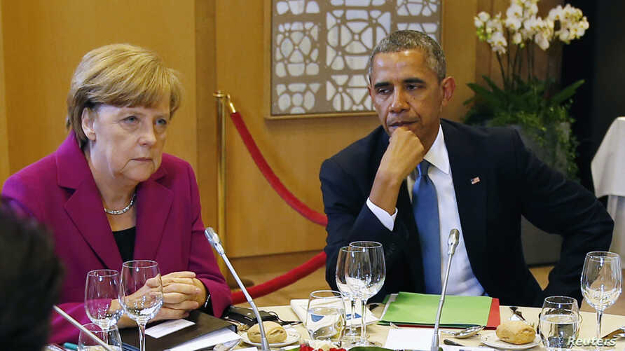 FILE - U.S. President Barack Obama (R) and German Chancellor Angela Merkel listen during the G7 Summit working dinner in Brussels.