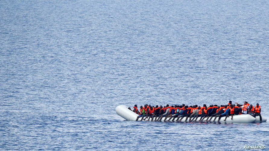 "Migrants wait to be rescued by ""Save the Children"" NGO crew from the ship Vos Hestia in the Mediterranean sea off Libya coast, June 18, 2017."