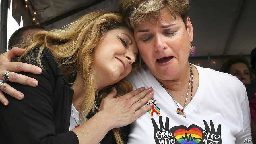 Pulse nightclub owner Barbara Poma comforts Orlando City commissioner Patty Sheehan, right, June 12, 2017, during a ceremony at the club in Orlando, Florida, on the one-year anniversary of the June 12, 2016, shooting that killed 49.