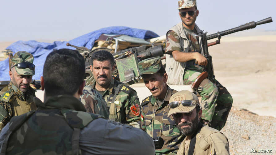 """Kurdish """"peshmerga"""" troops stand guard during an intensive security deployment on the outskirts of Sinjar, west of Mosul, Aug. 5, 2014."""