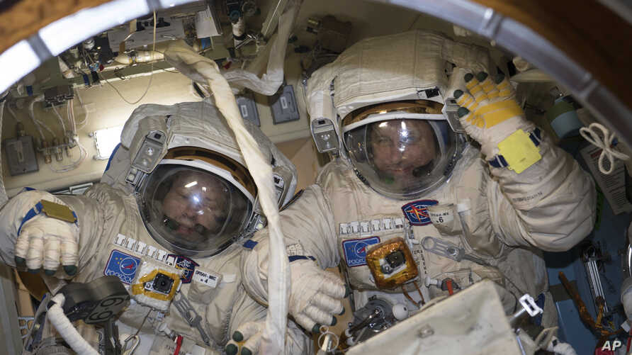 This Jan. 31, 2018 photo made available by NASA shows cosmonauts Alexander Misurkin, left, and Anton Shkaplerov in their Russian Orlan spacesuits during a fit check inside the International Space Station.