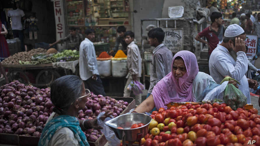 FILE - An Indian woman buys vegetables at a road side stall  in New Delhi, Aug. 20, 2014.