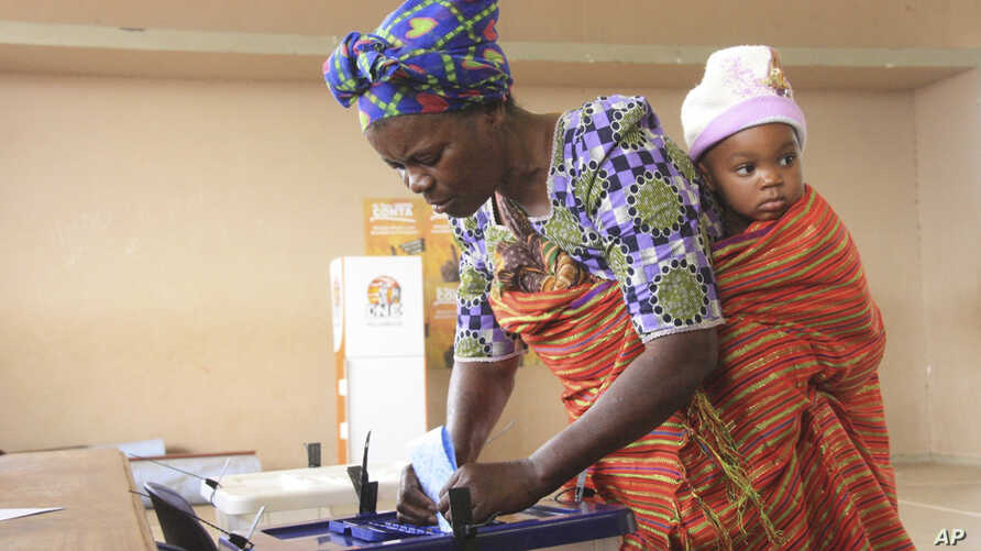 A woman with a child on her back casts her vote at a polling station as the country goes to the polls in Maputo, Mozambique, Oct. 15, 2014.