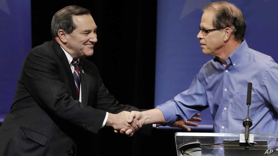 Democratic Sen. Joe Donnelly, left, shakes hands with Republican former state Rep. Mike Braun following a U.S. Senate Debate in Indianapolis, Oct. 30, 2018.