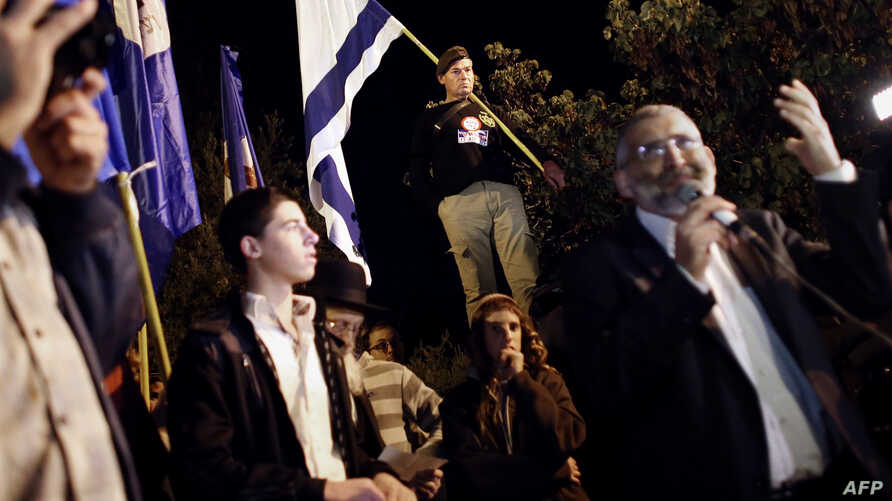 FILE - Israeli far right leader Michael Ben Ari (R) delivers a speech as Jewish extremists gather near the Old City of Jerusalem, Nov. 6, 2014.